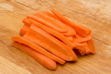 Closeup of sliced carrots placed  on wooden cutting board
