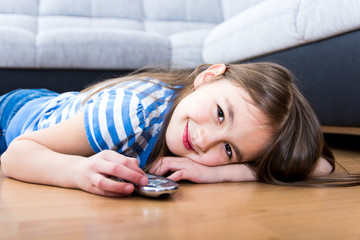 cute little girl holding a remote control