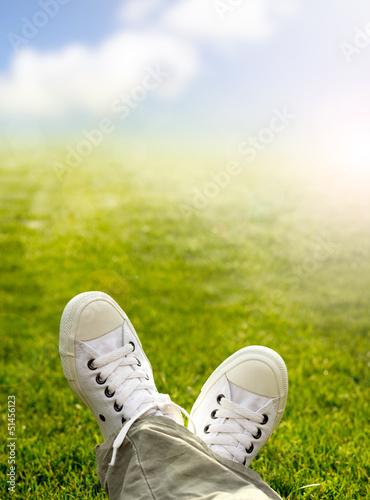 Sneakers in the grass with grass and sky background