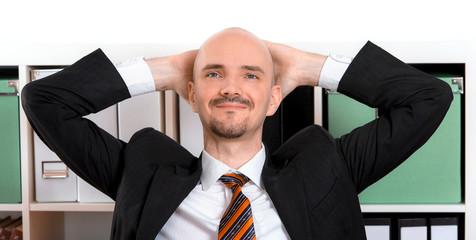 träumender Mann mit Hände hinter dem Kopf im Büro