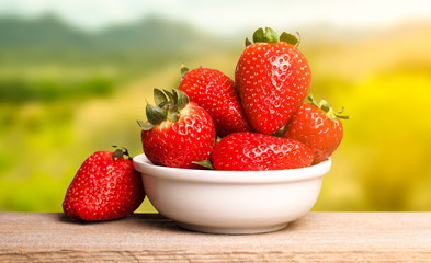 Strawberries in white plate on wooden table. Country background