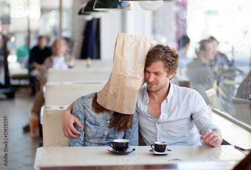 Young man hugging his girlfriend with a paper bag over her head.