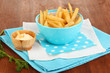 French fries in bowl on wooden table close-up
