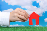 concept: woman hand with paper house on sky background, close