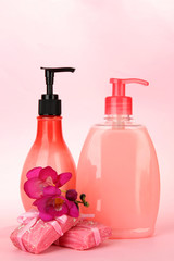 Liquid and hand-made soaps on pink background
