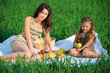 Happy girls on green grass with fruits