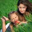 Happy girls on green grass with apple