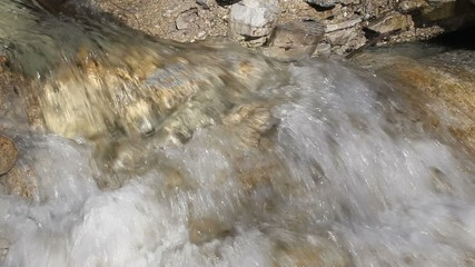 stream of water between the rocks in the mountains