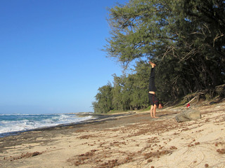 Man handstands on Lava rocks on North Shore Beach
