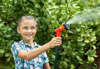 Young girl pours water from hose