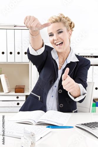 Toller Tag im Büro - Frau lachend am Schreibtisch