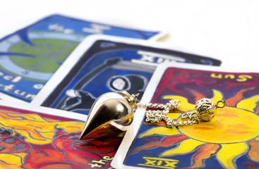 Silberpendel auf handgemalten Tarotkarten
