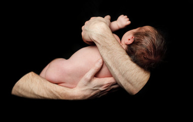 Safety concept - baby in comfort father's hands (shallow depth o