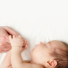 Baby and father's hands on white background