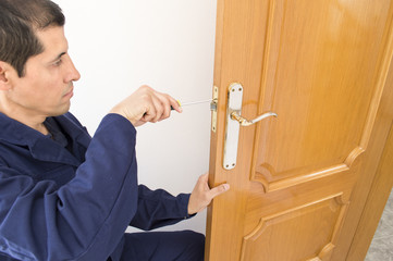 Carpenter fixing a lock in the door  with a screwdriver