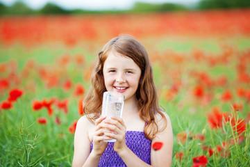 lächelndes mädchen trinkt mineralwasser