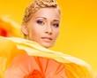 Beautiful young cheerful blond woman  among big yellow flowers