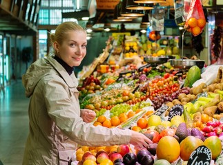 Young  woman choosing fresh fruits on market