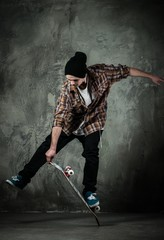 Young man in hat and shirt performing stunt on skateboard