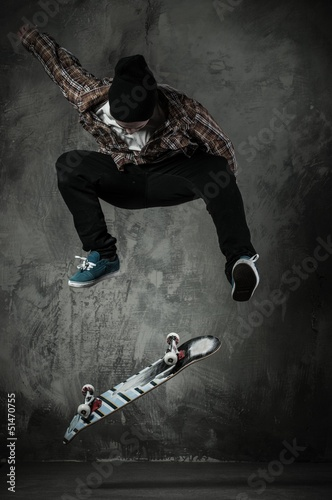 Fototapeta Young man in hat and shirt performing stunt on skateboard