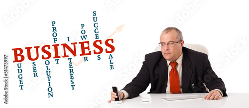 businessman sitting at desk and holding a mobilephone with busin