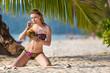 Girl with coconut on a tropical beach