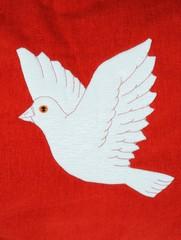 Christmas dove sewn onto red fabric © Arena Photo UK
