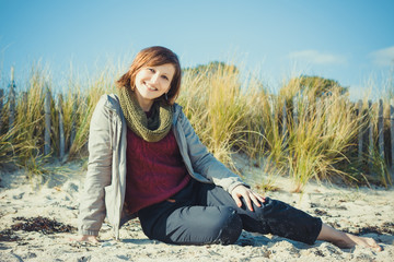 Young girl sitting on the beach in early spring and smiling happ