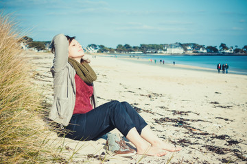 Young girl sitting on the beach in early spring and enjoy the su