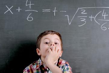 Schulkind mit Rechenaufgabe an Tafel