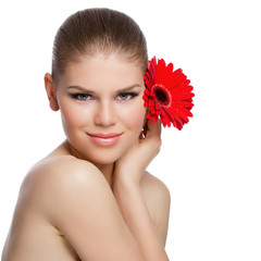 Skincare woman close-up. Young smiling female with red flower