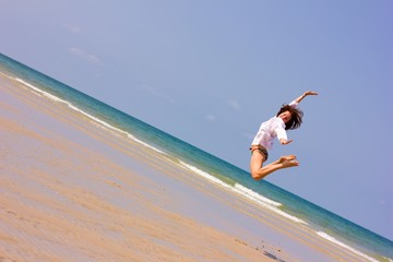 Young lady jumping over the horizon