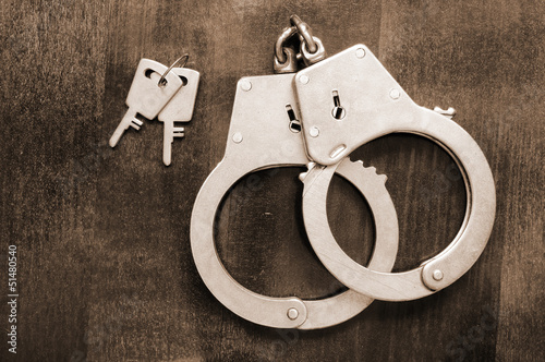 Steel metallic handcuffs with keys on wooden table