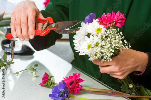Florist pruning flower bouquet.