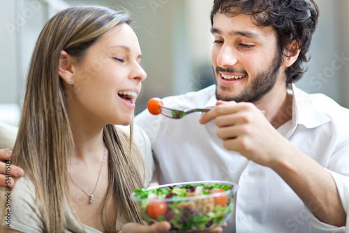 Happy couple eating a salad