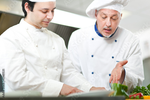 Two chefs cooking in a kitchen