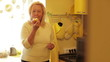 Senior woman eating apple in the yellow kitchen.