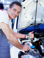 Car mechanic checks the antifreeze mixture of a car in a garage