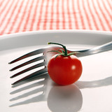 Cherry tomato and fork on plate