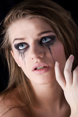Young crying woman on dark background