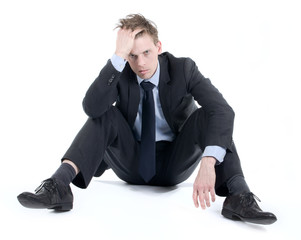 Depressed businessman sitting on the floor with hands in his hai