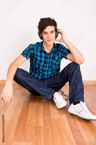 Young man listening music with headphones at home