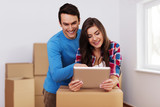Young and loving couple arranging relocation in new home poster