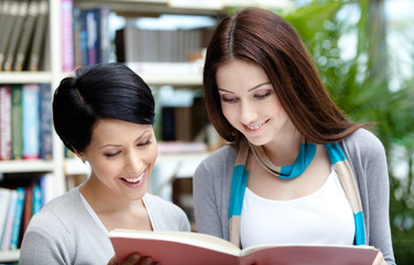 Two female students read books at the library hall