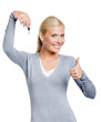 Thumbing up woman in gray sweater keeps a key