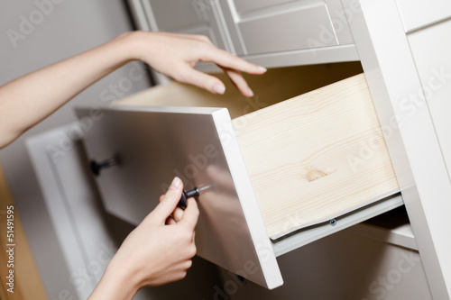 Close up view of hand opening a white drawer