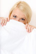 Girl in bed covers her face with white eiderdown