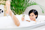 Woman taking a bath with suds drinks champagne