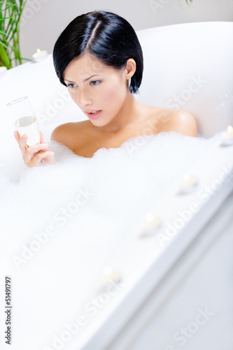 Woman taking a bath with suds and candles drinks fizz