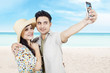 Asian couple take pictures at beach